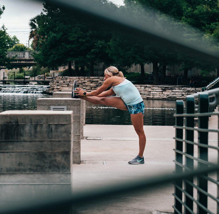 kobieta rozciągająca się po porannym biegu nad rzeką