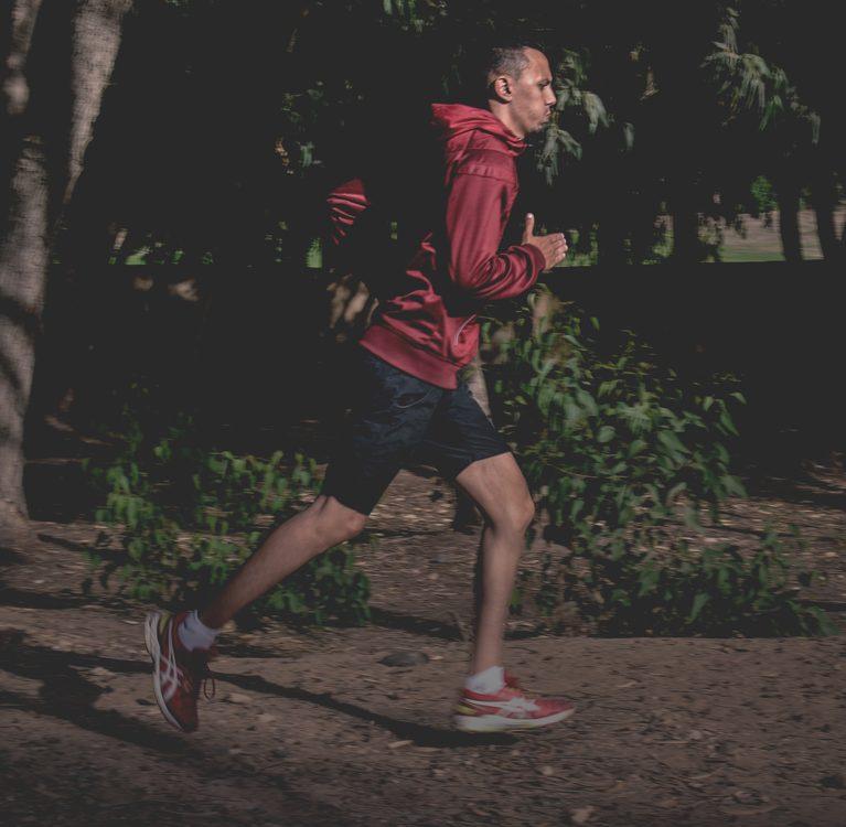 mężczyzna biegnący przez park