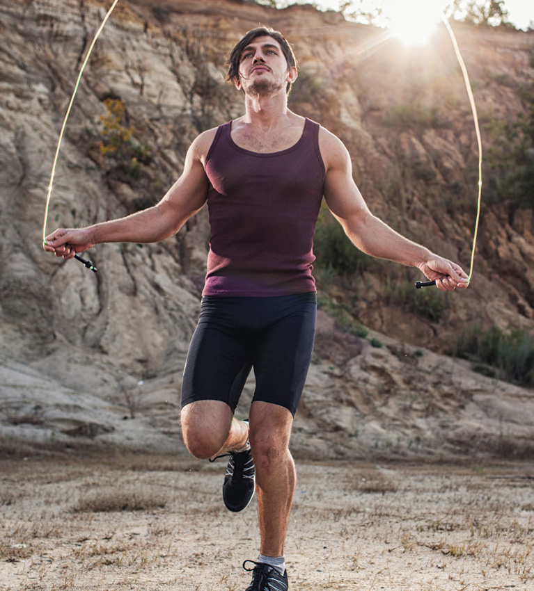 mężczyzna trenujący ze skakanką o poranku