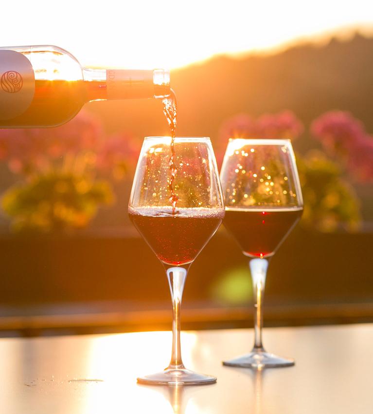 kieliszki napełniane winem przy zachodzie słońca